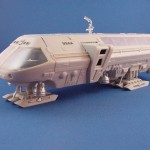 The Aurora kit of the Moon Bus from the classic film 2001: A Space Odyssey is shown both open and closed. Issued only once, this kit is highly sought on the collector's market. The model was painted with Railroad Colors bottle paints. The kit's front window glass is inaccurate because it was not used on the movie miniature. The glass should be on the inside window frame in front of the cockpit instrument panel. The interior colors of the cabin are guesses because the film's lighting was in a blue/green tint that distorted actual colors. The cockpit was painted from published color still publicity photos. By Ed Wahl