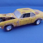The 1-32 Monogram kit of the 1969 Chevy Nova is shown as it might look 25 years later when an overeager restoration begins with new chrome wheels and white-letter tires while the rest of the car is rusted out and a little bent. The interior seats are torn and need replacement. The body was painted with Model Master flat yellow and dry-brushed with various weathering and rust colors. A Dremel router bit from behind created the holes in the body. A shot of Dullcote on the glass created the dirty look. By Ed Wahl